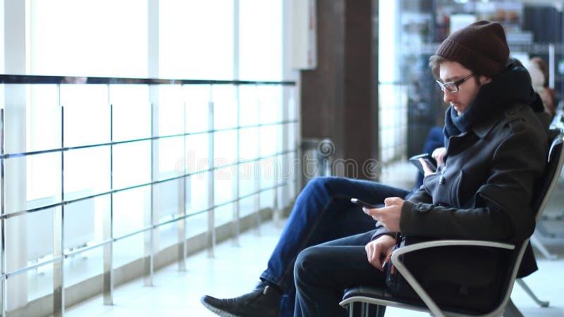 关闭 有坐在机场候诊室的智能手机的时髦人士 免版税库存照片