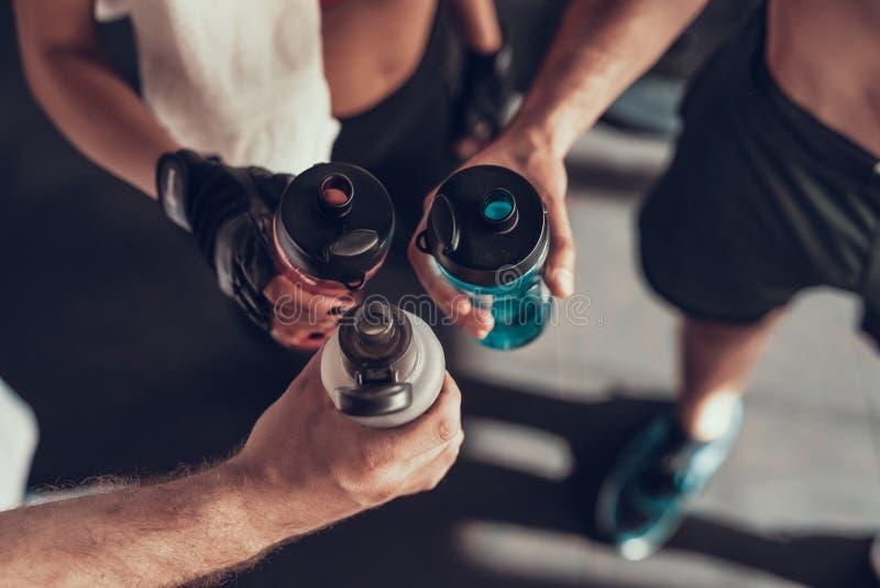 关闭 有瓶的三只手在健身房 库存图片