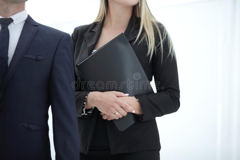 关闭 有连续站立与公司雇员的剪贴板的女商人 免版税库存图片
