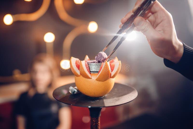 关闭 水烟筒人煤炭在葡萄柚碗变化 背景迷离,强光 库存图片