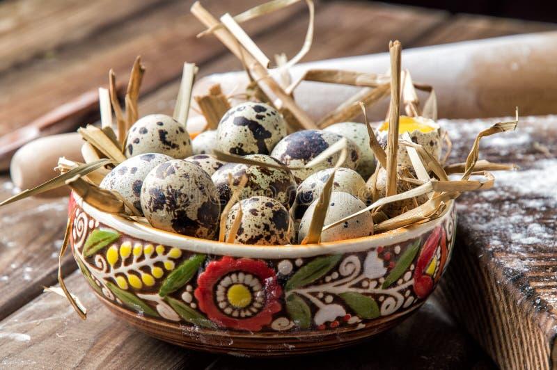 关闭 烹调一个传统复活节蛋糕 被绘的黏土碗用在干燥秸杆的鹌鹑蛋 背景棕色木 免版税库存照片