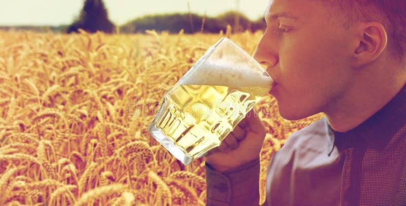 关闭年轻从玻璃杯子的人饮用的啤酒 免版税库存照片