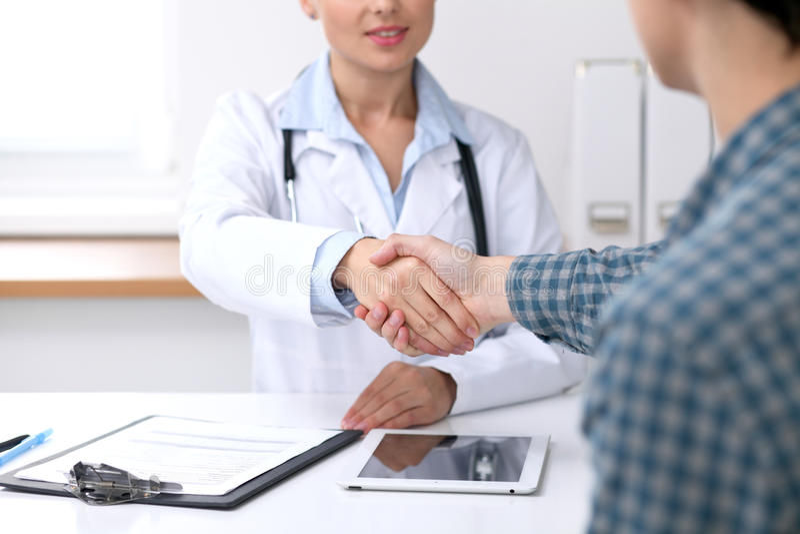 关闭医生妇女与她的男性患者握手 医学和信任概念 免版税库存照片