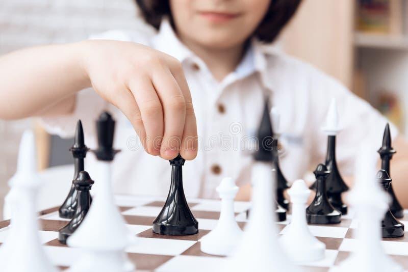 关闭 由主教的聪明的男孩移动 棋 免版税库存照片