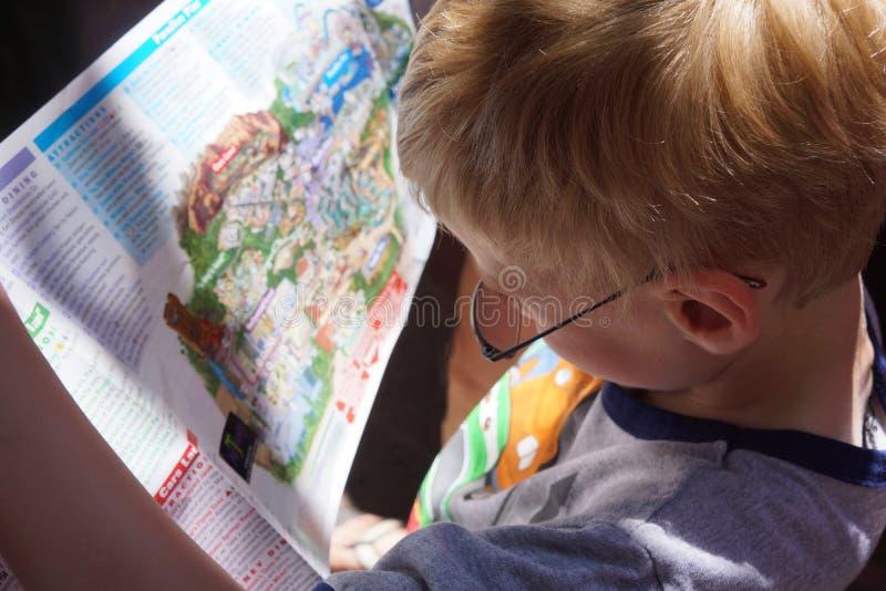 关闭年轻男孩读书地图 库存图片