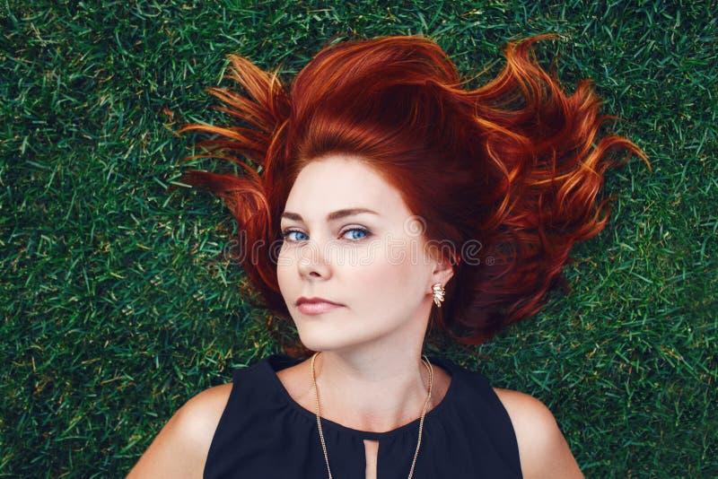 关闭年轻白种人美丽的女孩妇女画象有说谎在绿草的红褐色的头发的在公园 在视图之上 库存照片