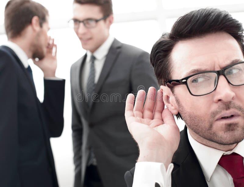 关闭 窃听在同事之间的交谈的商人 库存图片