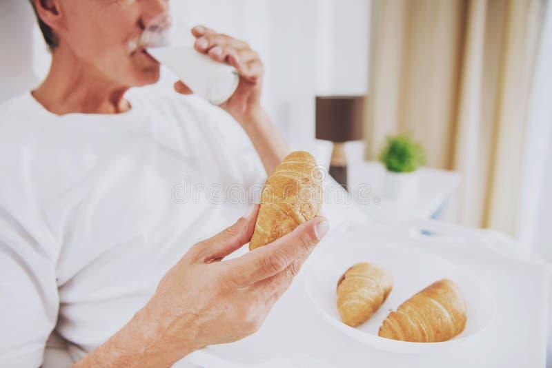 关闭 老人吃早餐在床在家 免版税库存图片