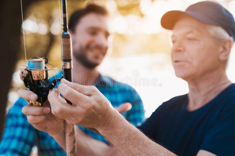关闭 老人检查渔转动的短管轴 一个人看老人 免版税库存图片