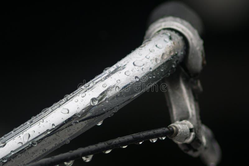 关闭/自行车把手的宏观图象在雨中与许多在钢的水滴 库存照片