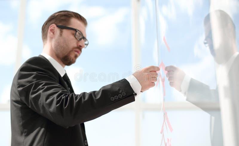 关闭 读贴纸笔记的商人在玻璃 库存图片