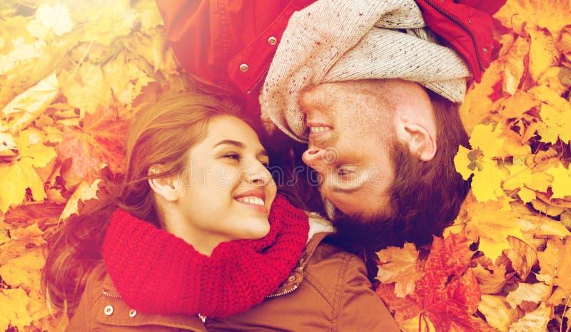 关闭说谎在秋叶的微笑的夫妇 库存图片