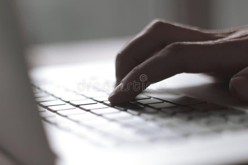 关闭 键入在膝上型计算机键盘的男性手的被弄脏的图象 库存照片