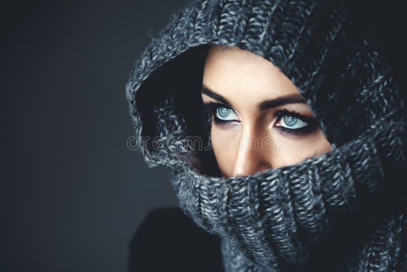 关闭头戴面纱,在她的面孔的顶头围巾的蓝眼睛的妇女/女孩演播室画象,举行它用她的手 图库摄影