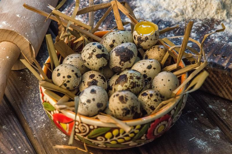 关闭 黏土碗充满干燥秸杆和新鲜的农厂鹌鹑蛋 土气的生活仍然 木背景 免版税图库摄影