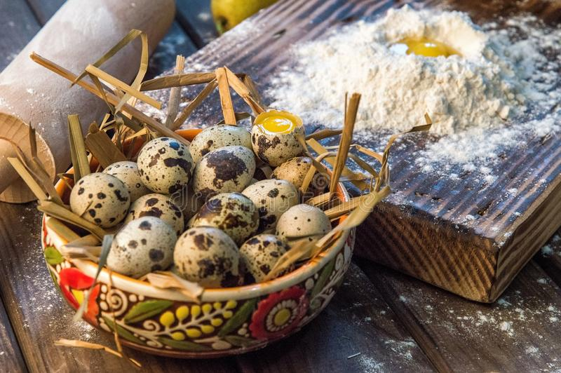 关闭 黏土碗充满干燥秸杆和新鲜的农厂鹌鹑蛋 烹调土气蛋糕 免版税图库摄影