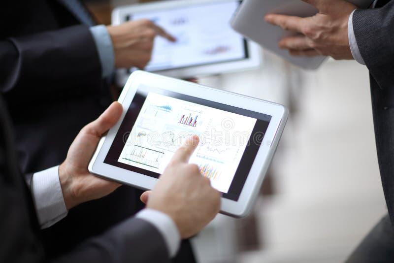 关闭 businessmens通过选项谈论销售日程表  库存照片