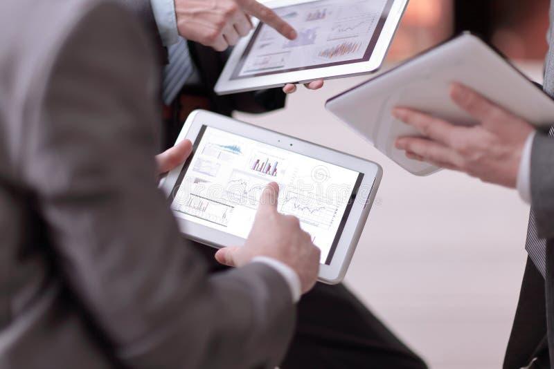 关闭 businessmens通过选项谈论销售日程表  免版税库存图片