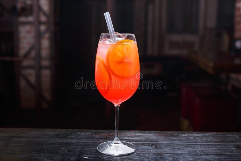 关闭aperol玻璃喷鸡尾酒,站立在酒吧柜台,在红灯背景 库存照片