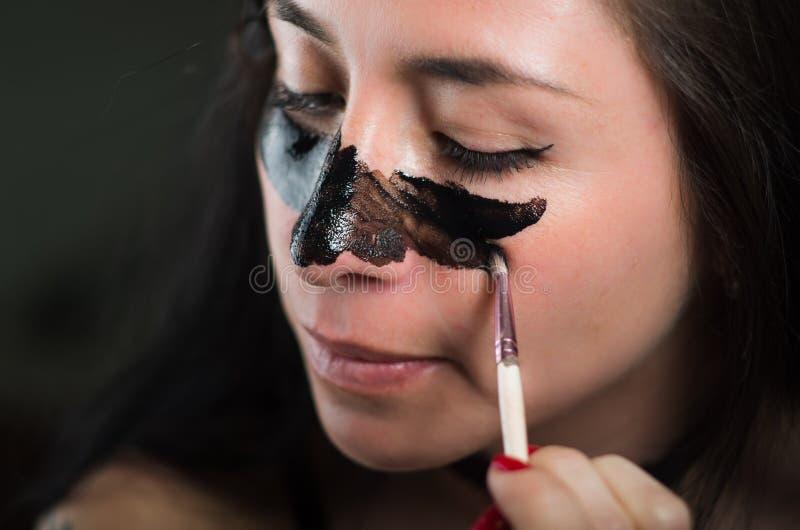 关闭aplying在她的面孔一个黑面具的秀丽少妇清洗皮肤 免版税库存照片