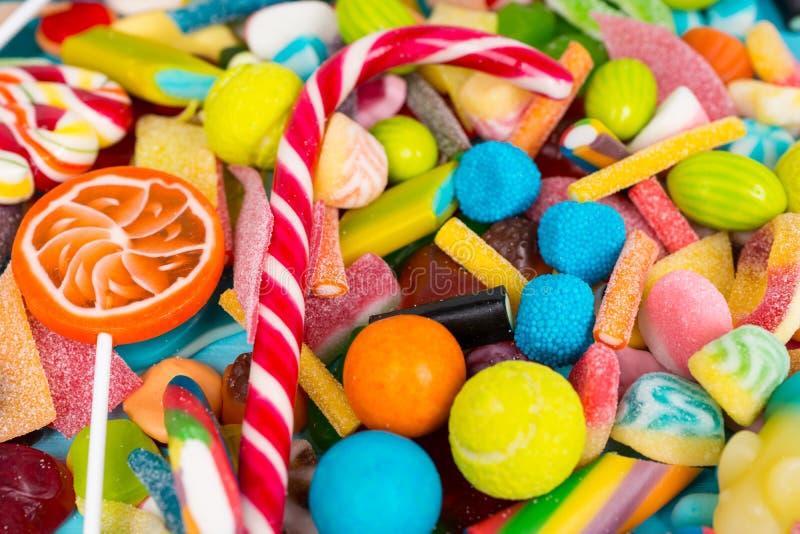 关闭cattered棒棒糖、嚼的甜点和果冻糖果 免版税库存照片