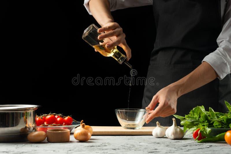 关闭chef& x27;s手,意大利西红柿酱为通心面做准备 薄饼 意大利烹调食谱的概念 库存照片
