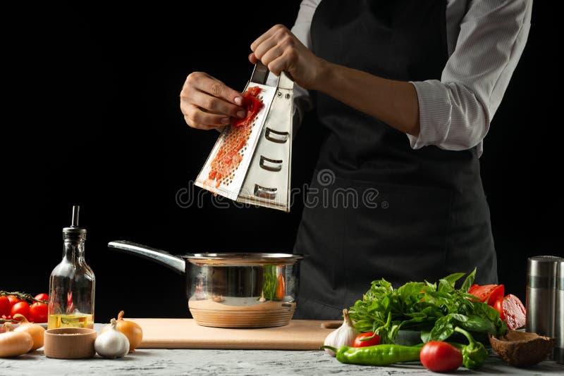 关闭chef& x27;s手,意大利西红柿酱为通心面做准备 薄饼 意大利烹调食谱的概念 免版税库存图片