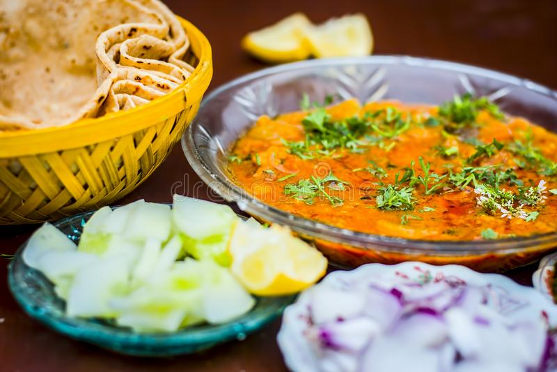关闭Dal makhani午餐的印地安膳食盘用切的黄瓜、葱和hari酸辣调味品与roti和白色Khichdi 库存图片