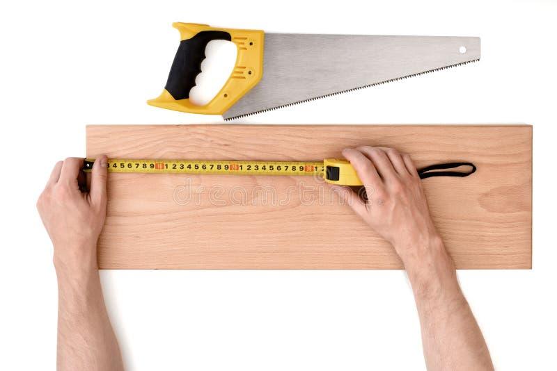 关闭man& x27的看法; s递与磁带线的测量的木板条,隔绝在白色背景 库存照片