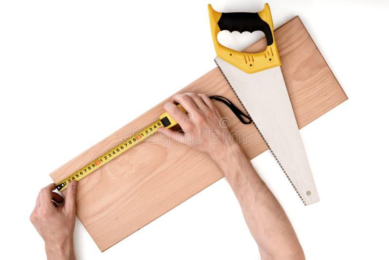 关闭man& x27的看法; s递与磁带线的测量的木板条,隔绝在白色背景 免版税库存图片