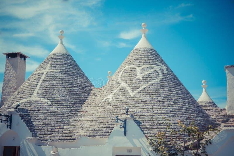 关闭Trulli房子的圆锥形屋顶有被绘的标志的 库存图片