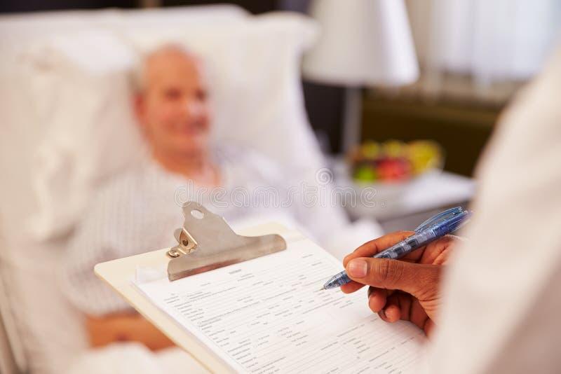 关闭Writing On Senior Male医生病人图表 库存照片