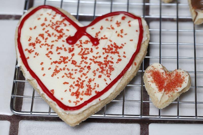 关系对心脏与白色结霜和红色的糖屑曲奇饼洒 代表关系 免版税库存照片