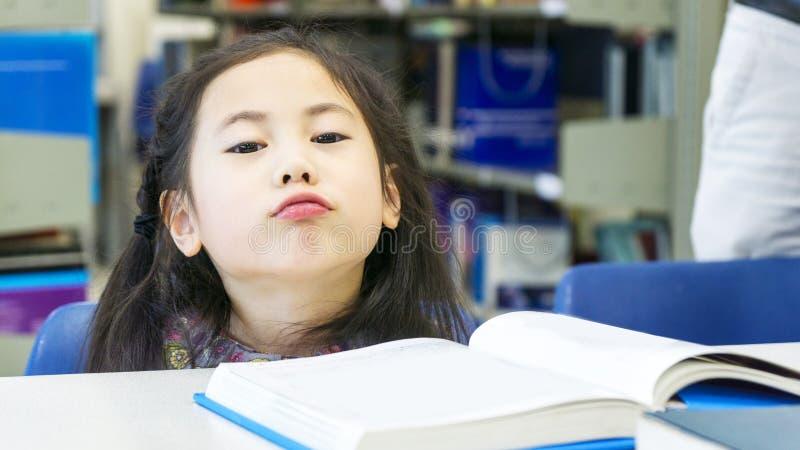 兴高采烈的亚洲逗人喜爱的女孩开会和阅读书在桌上 免版税库存图片