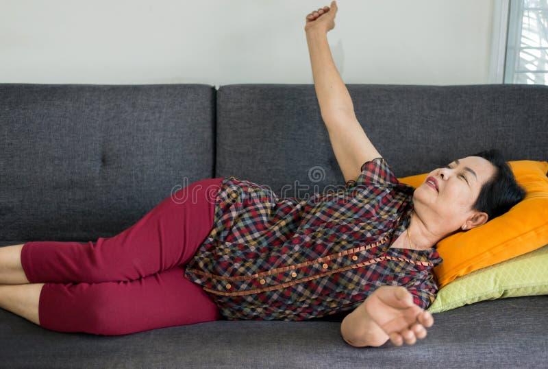 兴高采烈的亚洲高级女性,早上伸展着身子,在沙发上醒来 免版税库存图片