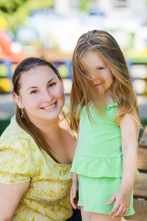 兴高采烈的卷发白肤金发的看照相机的女孩和她的母亲 库存图片