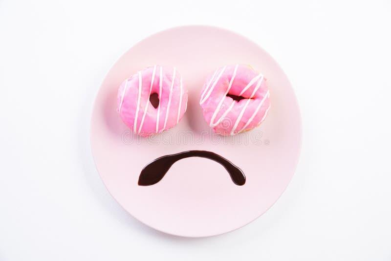兴高采烈的哀伤的面孔顶视图担心在与油炸圈饼作为眼睛和巧克力糖浆的盘做的超重作为在白色的嘴 免版税库存图片