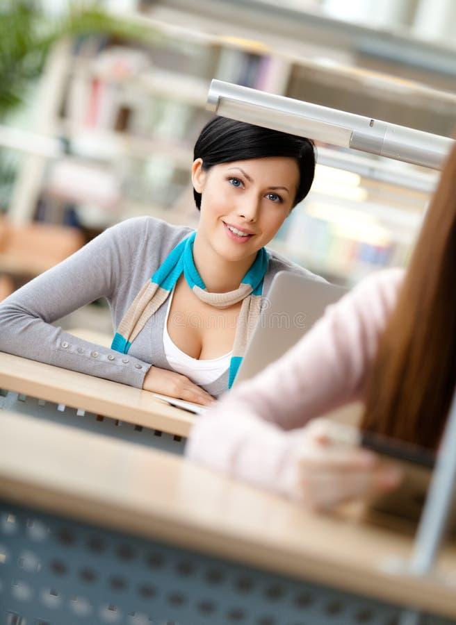 兴高采烈的妇女坐在服务台 免版税库存图片