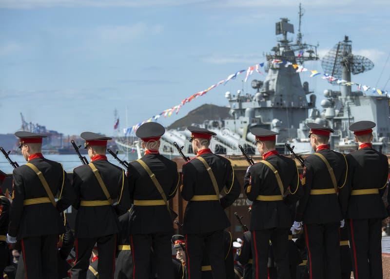 兵役的军事军校学生反对一艘军用船的背景 免版税库存照片