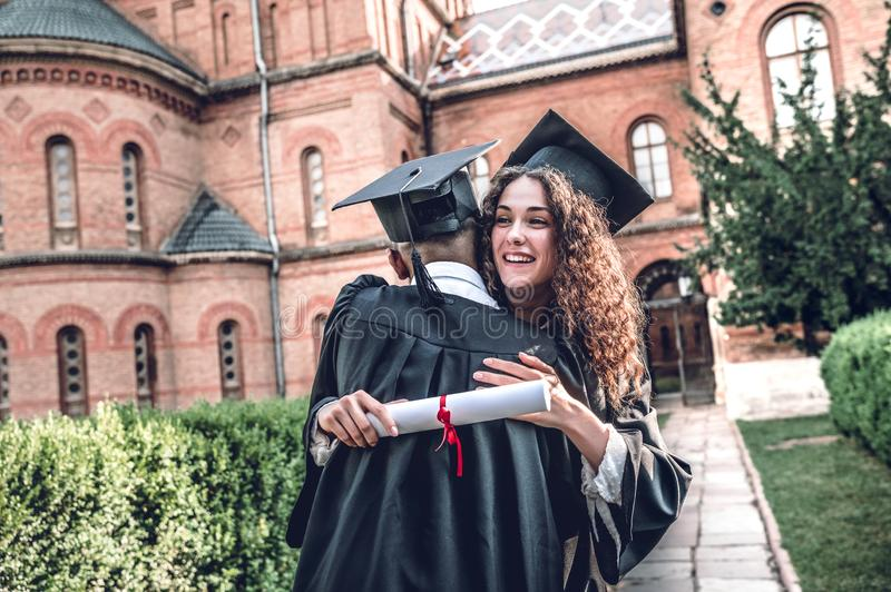 其中一我的生活的最愉快的片刻 愉快的毕业生在大学附近站立并且互相拥抱 图库摄影