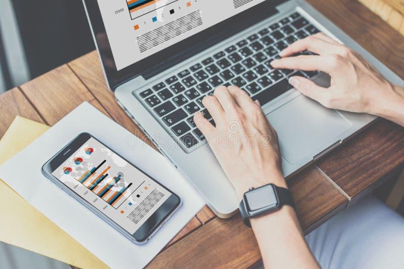 其次在木桌有图表、图和图的智能手机在屏幕上 免版税图库摄影
