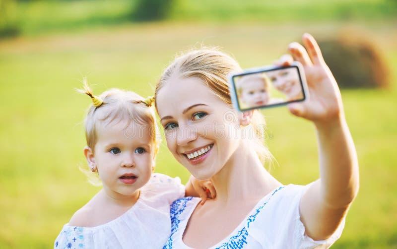 其他,拍摄selfie的小女儿由手机在夏天 免版税库存图片