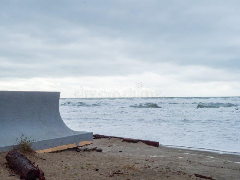 具体从波浪的防波堤保护的物产从在距离的一场不祥的风暴 免版税库存图片