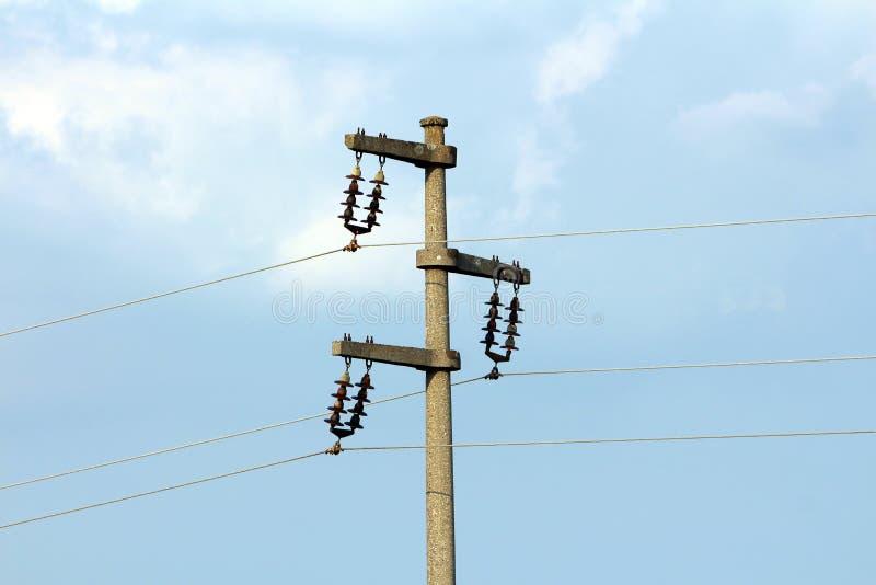 具体电能线与陶瓷绝缘体和三根被连接的导线的电线杆 库存图片