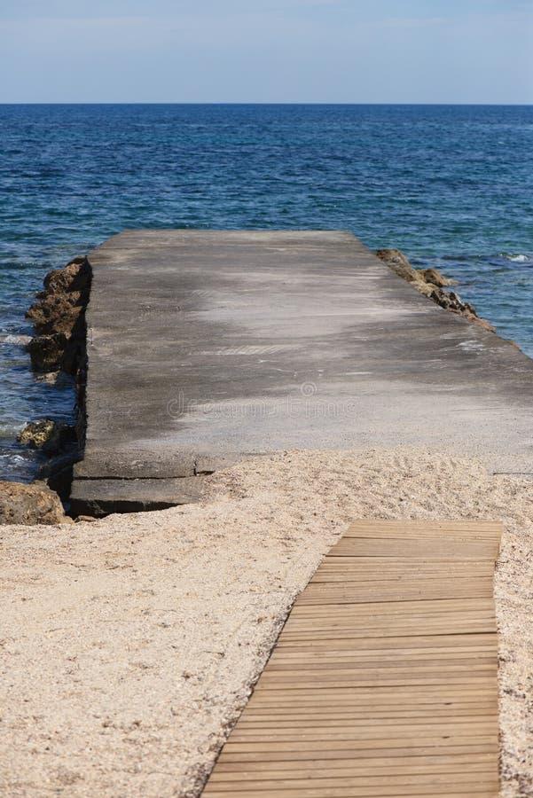 具体码头、木走道沙子和海 库存图片