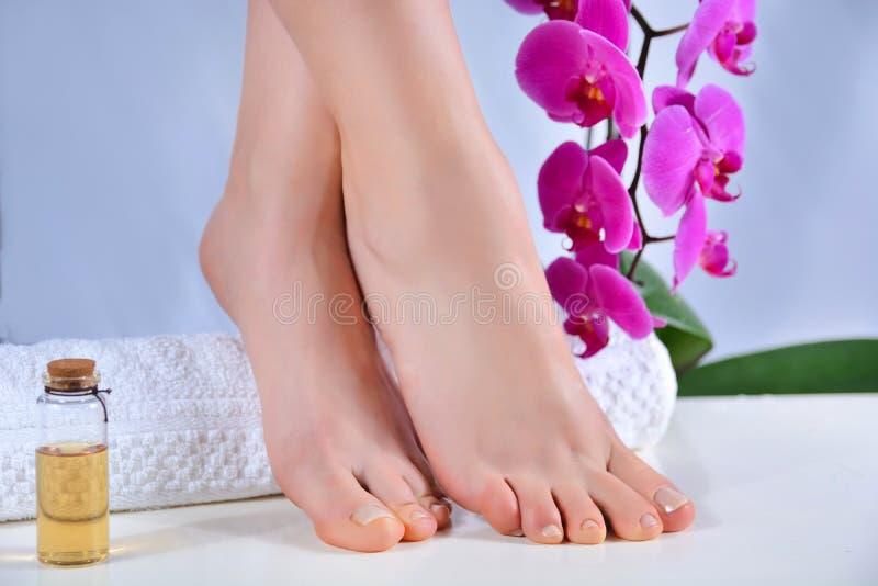 具有天然色彩钉蒂的女足及紫兰花装饰 免版税库存图片