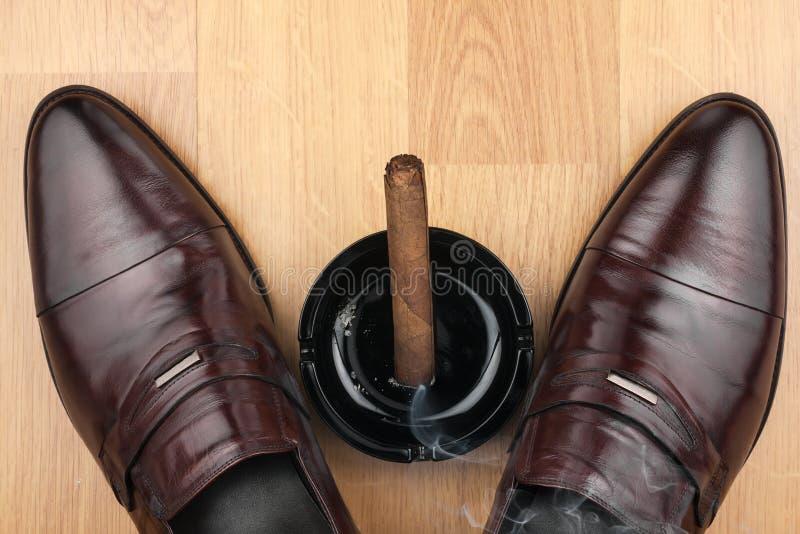 经典人的鞋子、烟灰缸和发怒的雪茄在木flo 免版税库存图片