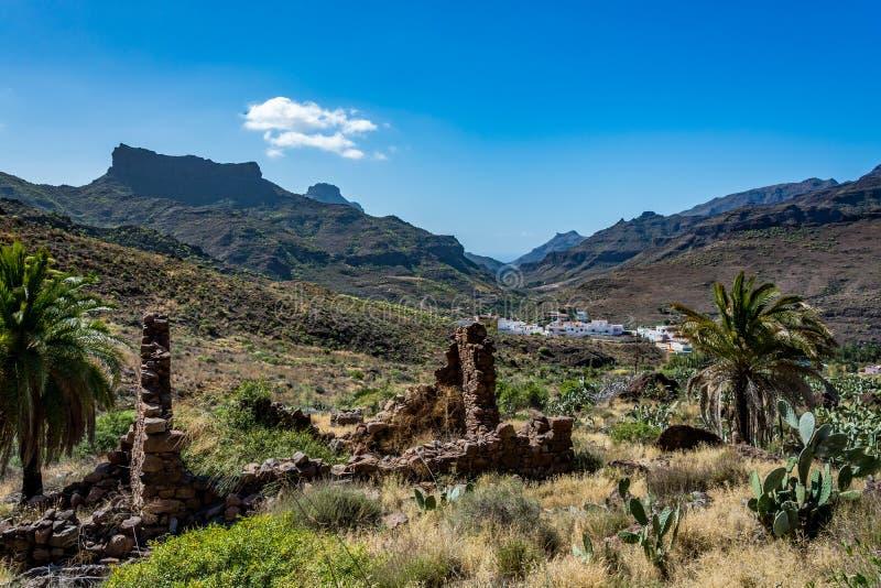 典型的山风景大加那利岛(盛大金丝雀)有前面的被破坏的老房子的 免版税库存照片