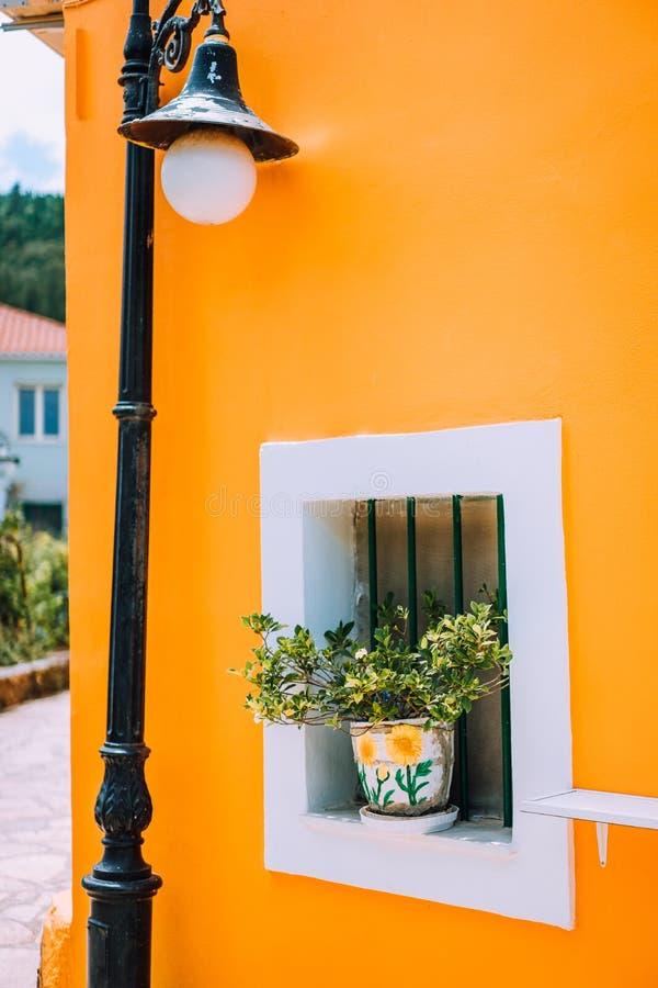 典型的希腊建筑学详述概念 橙色房子墙壁,在罐的花,灯笼,传统房子在希腊 免版税库存照片