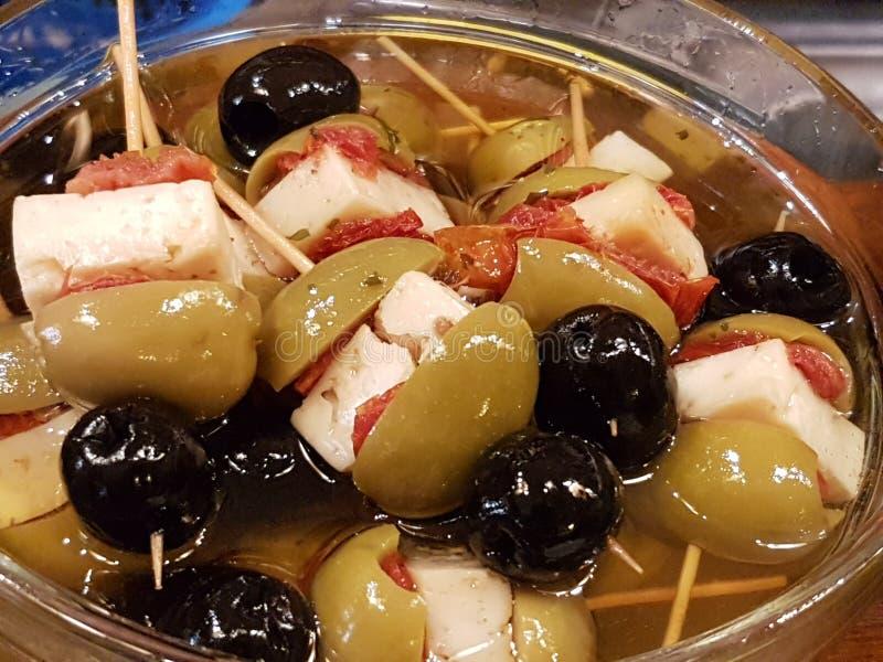 典型的开胃菜用黑橄榄、新鲜的干酪和红辣椒 库存照片
